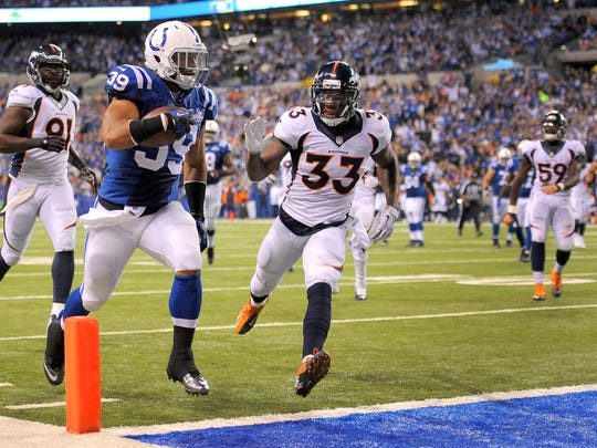 Indianapolis Colts' Stanley Havili (39) rushes the ball into the end zone ahead of Denver Broncos' Duke Ihenacho (33) during the first half of action. The Indianapolis Colts play the Denver Broncos Sunday, October 20, 2013, evening at Lucas Oil Stadium.