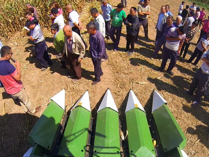 Farmers look over a combine during a DuPont Pioneer field demo day Wednesday, Sept. 4, 2014, in China's Shandong Province.
