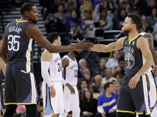 Golden State Warriors forward Kevin Durant (35) celebrates with guard Stephen Curry during the first half of the team's NBA basketball game against the Memphis Grizzlies in Oakland, Calif., Saturday, Dec. 30, 2017. The Warriors won 141-128. (AP Photo/Jeff Chiu)