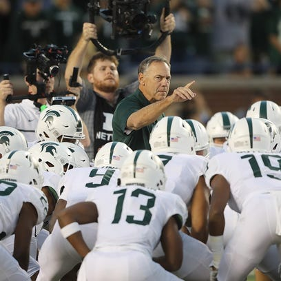 Michigan State coach Mark Dantonio huddles his team