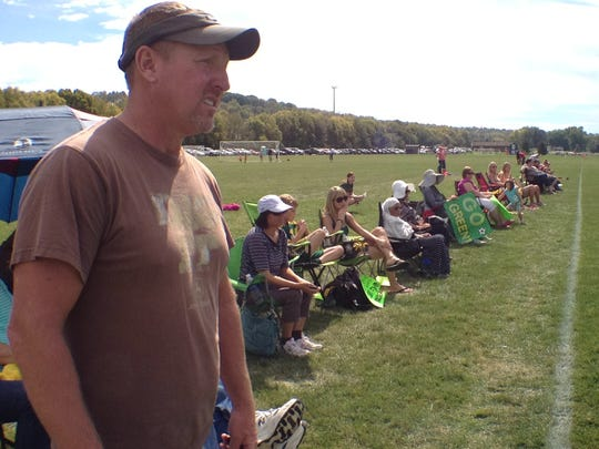 Soccer parent Mark Altemeier quietly takes in the game action. Other parents brought signs that they held up instead of shouting.