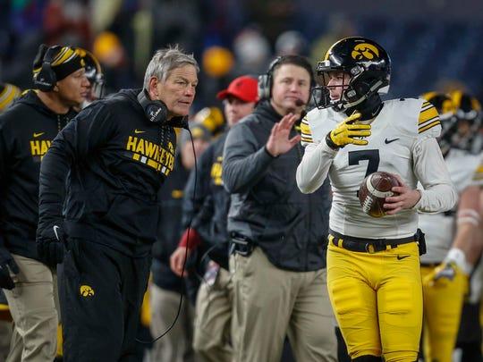 Iowa head football coach Kirk Ferentz talks with punter
