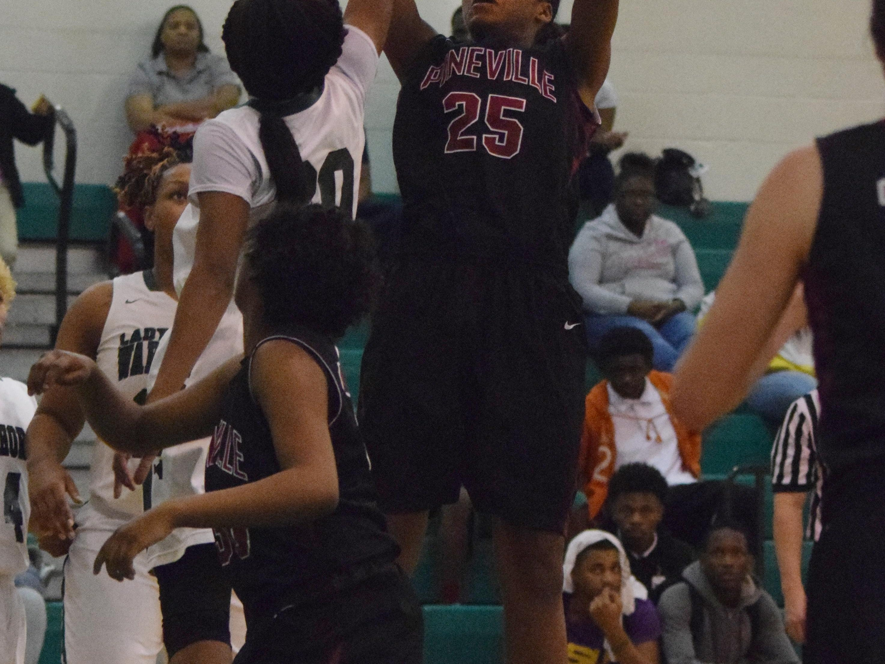Pineville's Krystal Freeman (25) shoots over Peabody's Azia Reed (20, left) Tuesday.