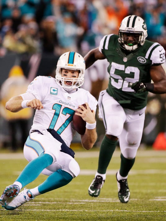 Miami Dolphins quarterback Ryan Tannehill (17) slides to avoid a hit against the New York Jets during the second quarter of an NFL football game, Monday, Dec. 1, 2014, in East Rutherford, N.J. (AP Photo/Julio Cortez)
