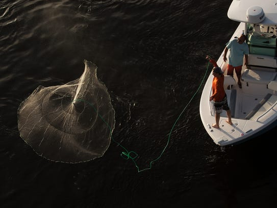 Fishermen toss a castnet in search of bait off the