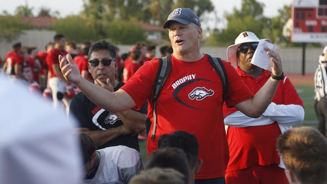 Brophy Prep's head coach Jon Kitna talks to his team on the sideline during an exhibition at Brophy College Prep in Phoenix, Ariz. on Aug. 9, 2018.