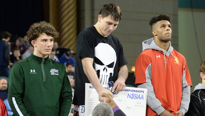 Delsea's Billy Janzer stands atop the podium after defeating Bergen CatholicÕs Josh McKenzie in the 182-lb state final match at Boardwalk Hall in Atlantic City on Sunday.