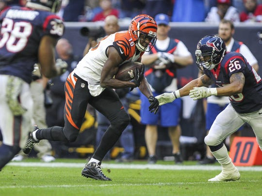 Nov 23, 2014; Houston, TX, USA; Cincinnati Bengals wide receiver A.J. Green (18) makes a reception during the first half as Houston Texans defensive back Darryl Morris (26) attempts to make a tackle at NRG Stadium. Mandatory Credit: Troy Taormina-USA TODAY Sports
