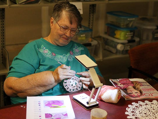 Volunteer Marcia Ingham crochets a coaster at the grand