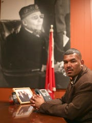 Student minister Troy Muhammad sits in front of a large photo of the Honorable Elijah Muhammad in his office at Muhammad's Mosque No. 1 in Detroit on February 18, 2014.