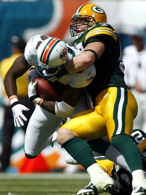 Green Bay Packers linebacker A.J. Hawk tackles Miami Dolphins receiver Derek Hagan during the first half at Dolphin Stadium in Miami on Oct. 22, 2006. That was the last time the Packers played in Miami.