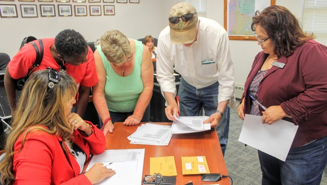 Otero County Clerk Denise Guerra (right) assists poll workers in certifying ballots Friday at the county commission chambers.