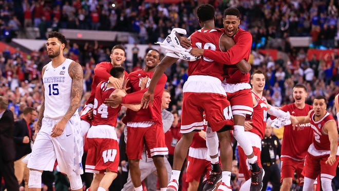 Kentucky's Willie Cauley-Stein walks back to his bench as Wisconsin players celebrate a 71-64 win in the semifinal Saturday at the Final Four at Lucas Oil Stadium. By Matt Stone, The C-J April 4, 2015.