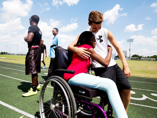 East Lee County High School track athlete Crystal Christopher gets a hug from friend and handler Connor Blais. Christopher has Cerebral palsy. She is competing in several events in the LCAC track and field meets.