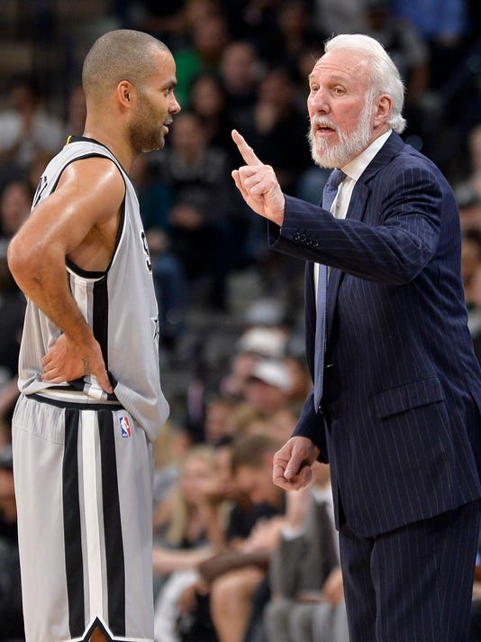 San Antonio Spurs head coach Gregg Popovich, right, talks to Spurs guard Tony Parker, of France, during the second half of an NBA basketball game against the Denver Nuggets, Saturday, Feb. 4, 2017, in San Antonio. (AP Photo/Darren Abate)