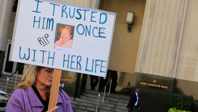"""Michelle Mannarino, of Waterford, Mich., holds a sign with the photo of her mother who had been under the treatment of Dr. Farid Fata, outside Federal Court in Detroit on Thursday, Oct. 2, 2013.  """"We trusted him once,"""" said Mannarino. Fata has since pleaded guilty to intentionally misdiagnosing patients and ordering unnecessary treatments."""