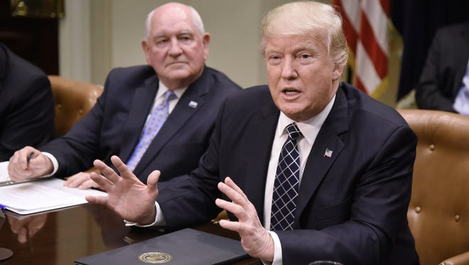 President Donald Trump speaks as Secretary of Agriculture Sonny Perdue looks on after signing the Executive Order Promoting Agriculture and Rural Prosperity in America during a roundtable with farmers in the Roosevelt Room of the White House in Washington, D.C., on April 25.