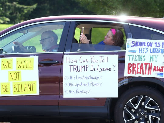 Activists participate in a People's Motorcade from