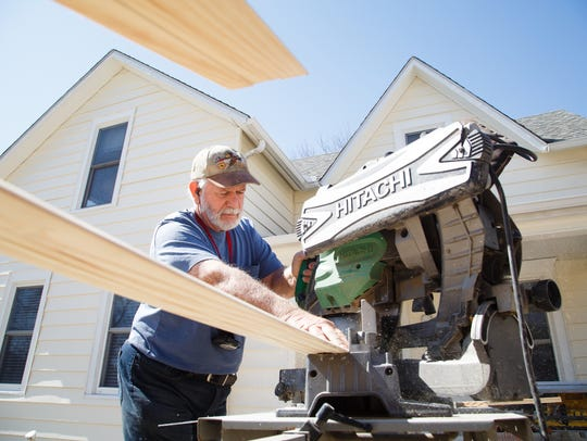 Paul Fay cuts trim work for a home he is working on owned by Conni Delinger in Stanton. A California transplant, Delinger discovered Stanton on a cross-county trip and bought this house. She then purchased another on the city's Main street.
