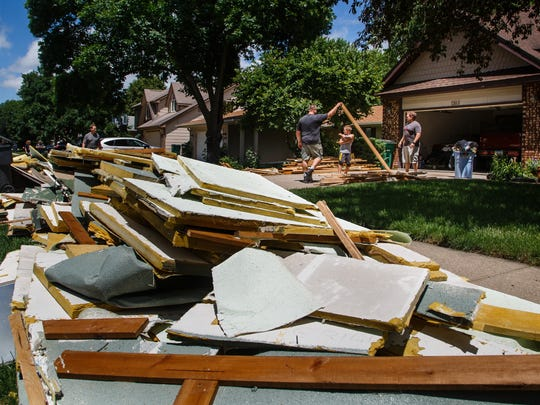 Steve Lucas of Waukee, right, helps sort through the wood he, brother Eric Bauer, left, and BauerÕs son Austin, 7, center, tore out of their parents basement on Sunday, July 1, 2018, in Clive. They said there was about eight inches of water in the basement and everything needed to go.