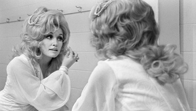 Primping before the mirror in the dressing room backstage, Dolly Parton prepares to please her fans at the RCA Records breakfast and show at the Municipal Auditorium in 1973.