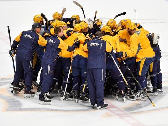 The Nashville Predators huddle up during practice at