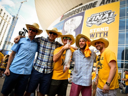 Fans pose with a catfish before Game 3 of the Stanley