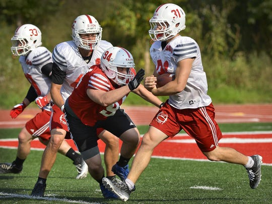 St. John's University senior standout running back Sam Sura (31) carries the ball around freshman defensive lineman Ted Kalina (94) in practice Tuesday at Clemens Stadium.