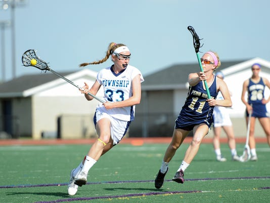 Manheim Township's Emily McBride pushes past Penn Manor's Hannah Brown in the opening round of the District 3 playoffs. The Blue Streaks defeated the Comets 22-4 at Manheim Township High School on Tuesday, May 12, 2015. Patrick Blain for GameTimePA.com