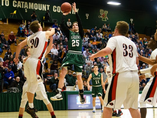 St. Johnsbury's Logan Wendell (25) shoots the ball over Rutland's Ethan Notte (30) during the Division I boys basketball semifinal game between the St. Johnsbury Comets and the Rutland Raiders at Patrick Gym on Thursday night March 15, 2018 in Burlington.