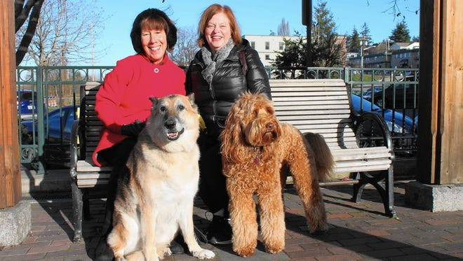 Kathy Denney, left, with German shepherd Shelby, and Tessa Rawitzer, with Australian labradoodle Arnold, take a break from dog walking in Bellingham, Wash. Exercise and socialization are good for humans as well as dogs, Rawitzer says.