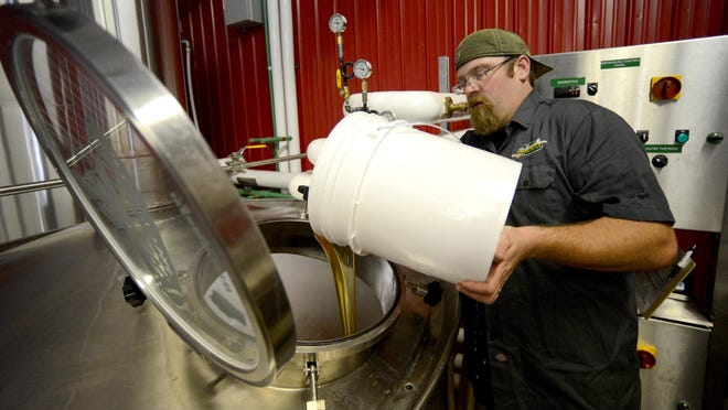 Brad Stillmank, founder and owner of Stillmank Brewing Co. in Green Bay, pours honey into the kettle while brewing The Bee's Knees at his brewery.