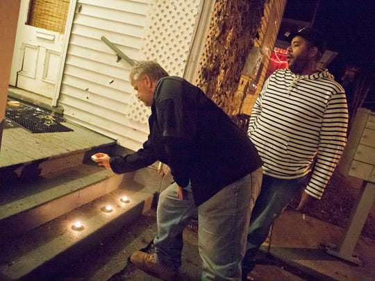 Butch Kelly of Colchester, left, places a candle after Isaac Hunter of Burlington left a similar tribute on the doorstep of Kenneth Stephens' home on Elmwood Avenue Wednesday evening, Dec. 23, 2015. Police shot and killed Stephens, 56, during a drug raid at his home Tuesday night.