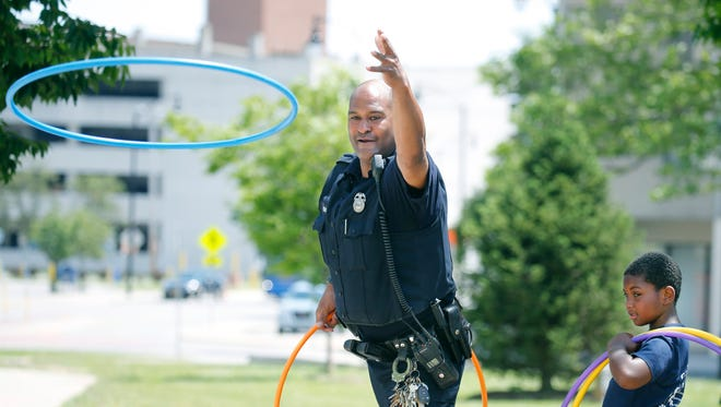 Officer Walt Sanders throws a hoop towards a cone next to Eddie Terry, 6, during the Rochester Juneteenth Celebration at Dr. Martin Luther King Jr. Memorial Park at Manhattan Square.
