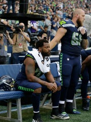 Seattle Seahawks center Justin Britt, right, stands next to defensive end Michael Bennett as Bennett sits on the bench during the singing of the national anthem before the team's NFL football preseason game against the Minnesota Vikings.