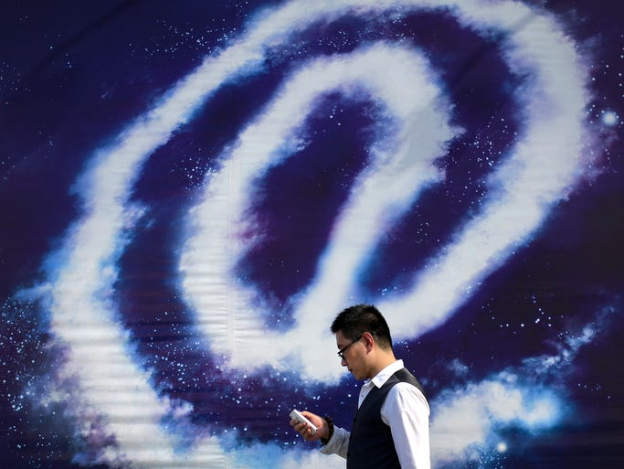 "A Chinese man checking on his smartphone walks past an ""at"" sign on display on a street in Beijing, China Thursday, Sept. 4, 2014. The editor-in-chief and several employees of an influential Chinese financial news site were taken away by police in an investigation over allegations that the executives and journalists had extorted money from companies by threatening to publish negative news about them, the official Xinhua News Agency said Thursday. (AP Photo/Andy Wong)"