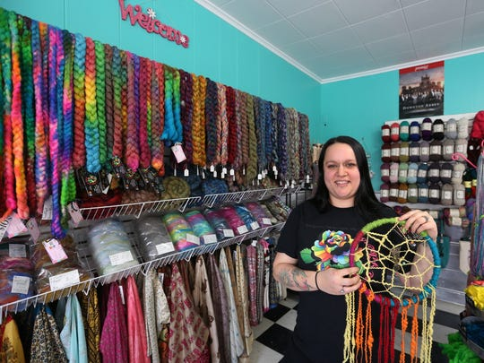 BritnyLe Gosz, 26, poses for a portrait with a dreamcatcher that she made with yarns in her yarn shop, Lucky Rose Fibers, in downtown Manitowoc on Tuesday, March 22. Gosz started selling her angora rabbit hair yarns online in 2013 and her business expanded fast, so she opened a physical shop in February.