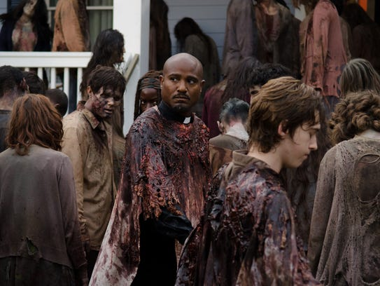 Father Gabriel (Seth Gilliam), center, and other humans