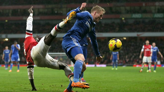 Chelsea's Andre Schuerrle, right, fends off the tackle of Arsenal's Bacary Sagna during their English Premier League soccer match between Arsenal and Chelsea at the Emirates stadium in London, Monday, Dec. 23, 2013.