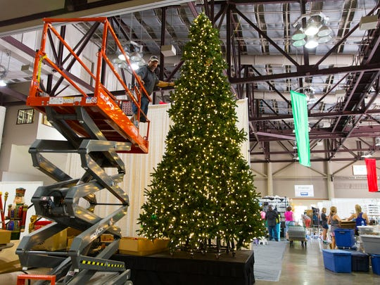 Workers set up a Christmas tree in the Cajundome Convention Center for Tinsel & Treasures fundraiser, to be held this weekend, Sept. 19, 2016 in Lafayette.