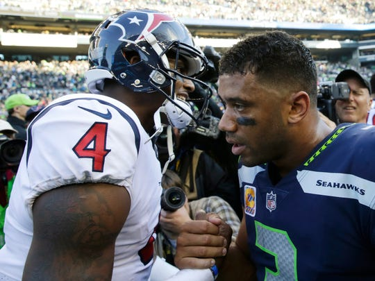 Houston Texans quarterback Deshaun Watson (4) shakes hands with Seattle Seahawks quarterback Russell Wilson, right, after an NFL football game, Sunday, Oct. 29, 2017, in Seattle. The Seahawks won 41-38. (AP Photo/Stephen Brashear)