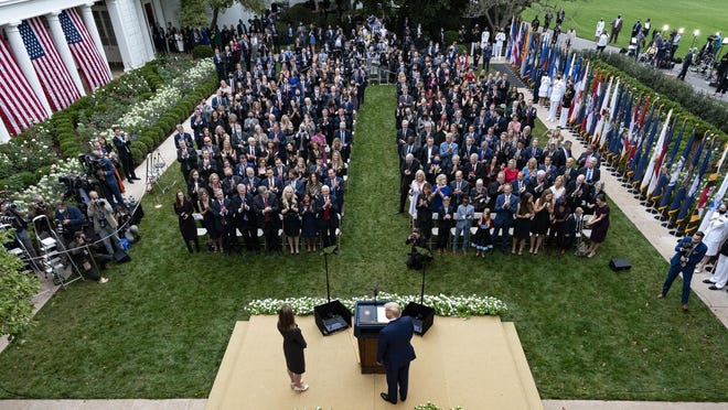 In this Sept. 26, 2020, photo President Donald Trump, center, stands with Judge Amy Coney Barrett as they arrive for a news conference to announce Barrett as his nominee to the Supreme Court, in the Rose Garden at the White House in Washington. Former New Jersey Gov. Chris Christie watches from fourth row from front on far right.