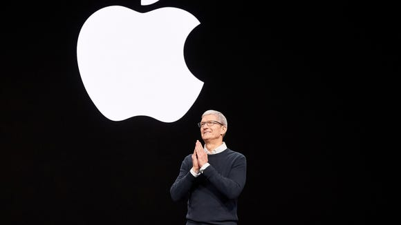 Apple CEO Tim Cook on stage with the Apple logo on the screen behind him
