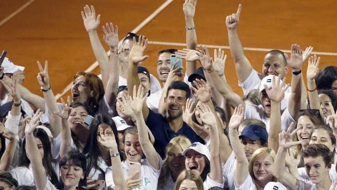 In this photo taken on Sunday, June 14, 2020, Serbia's Novak Djokovic, centre, poses with volunteers and players after the Adria Tour charity tournament in Belgrade, Serbia. Djokovic's charity tennis exhibition series combined with an overall softening of coronavirus restrictions in Serbia has led to a spike in the number the positive cases among professional athletes. Two tennis players ranked among the top 40 in the world and five players at Serbia's biggest soccer club have tested positive for the virus after being involved in sporting events where fans packed into the stands and social distancing was not enforced.