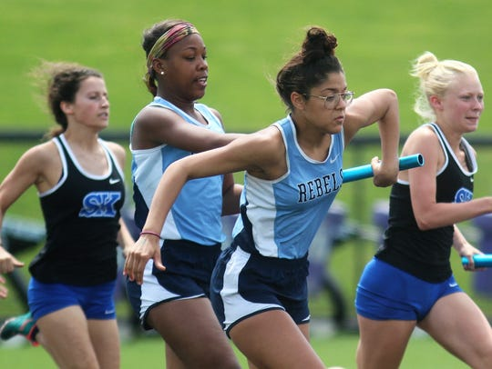 Runners hand off in the 4x100 relay during the KHSAA