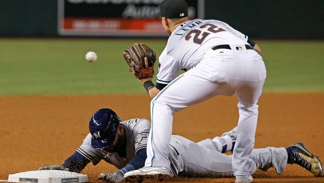 Milwaukee Brewers base runner Jonathan Villar, left, slides safely into third base after a double and a fielding error as Diamondbacks third baseman Jake Lamb waits for the late throw during the first inning on Friday, Aug. 5, 2016, in Phoenix.
