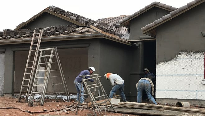 Workers finish plastering a house with stucco in a subdivision in Sierra Vista in December 2017. A new program in Cochise County that began in early January 2018 aims to fill vacant jobs in construction with unemployed former inmates.