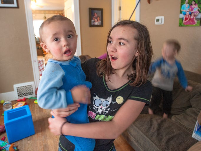 Jade Bishop holds her brother Joshua Kus, 1, at their
