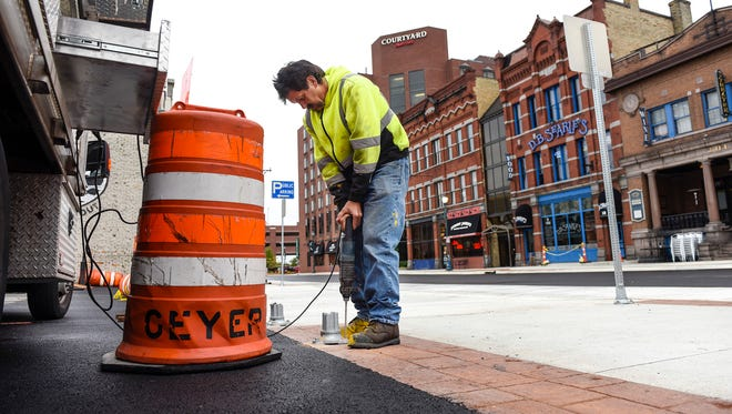 Scott Luckman, St. Cloud Public Works, drills holes and bolts down bases for signage as the final touches are completed Monday, Sept. 25, on the Fifth Avenue revitalization project.