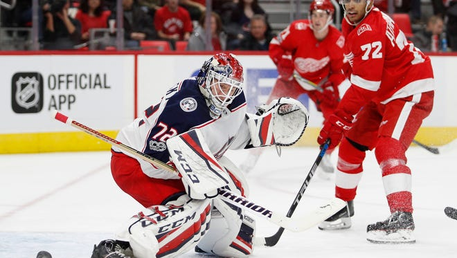 Blue Jackets goalie Sergei Bobrovsky (72) and Red Wings left wing Andreas Athanasiou (72) watch the puck go wide of the net during the second period of the Wings' 2-1 loss in a shoot-out on Saturday, Nov. 11, 2017, at Little Caesars Arena.
